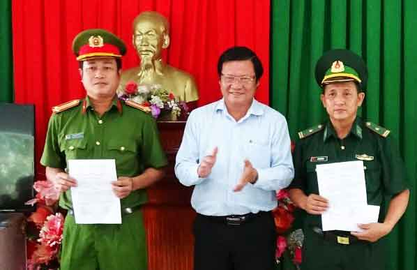 Director of the Department of Industry and Trade Le Minh Duc (C) gives an reward decision to police and army border forces for combating cigarette smuggling in Long An province