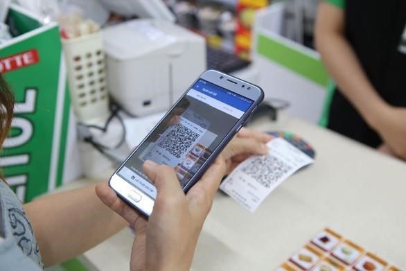 A customer makes payment by QR code at a supermarket (Photo: VNA)