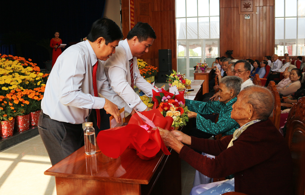 Secretary of the District Party Committee, Chairman of the District People's Council - Nguyen Van Dat (L) and Chairman of the District People's Committee - Lam Hoa Xung gives flowers to the Hero Vietnamese Mother