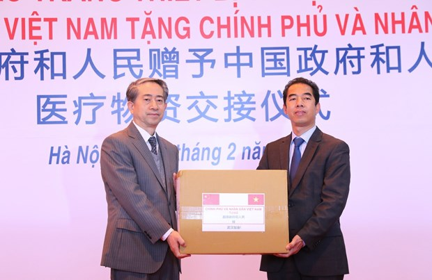Deputy Minister of Foreign Affairs To Anh Dung (R) hands over the assistance to Chinese Ambassador Xiong Bo at the ceremony at Noi Bai International Airport in Hanoi on February 9 (Photo: VNA)