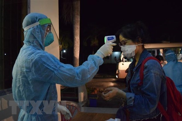 Checking temperature for a Vietnamese citizen returning home from abroad (Illustrative photo: VNA)