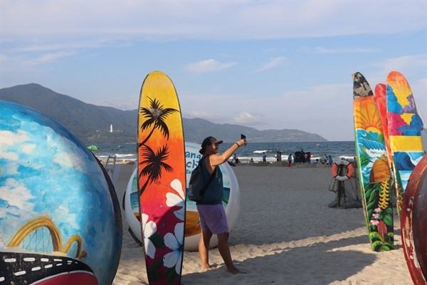 A tourist poses on a beach of Da Nang city before social distancing is re-imposed in the city following the confirmation of several new COVID-19 cases in the city. (Photo http://baovanhoa.vn)